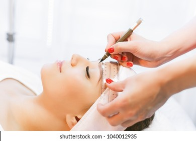 Beautiful young girl with long eyelashes tweezing her eyebrows in a beauty salon. Eyebrow Correction. Beauty Concept. Permanent Makeup. Microblading brow.  Beautician Doing brows Tattooing.