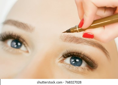 Beautiful young girl with long eyelashes tweezing her eyebrows in a beauty salon. Beauty Concept. Permanent Makeup. Microblading brow.  Beautician Doing eyebrow Tattooing. Close up view of blue eyes.