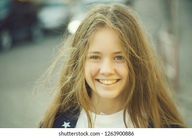 Beautiful young girl with long hair and smiling face outdoor closeup