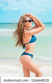 A beautiful young girl with long hair in a blue swimsuit  relax on beach in the sea in sunny hot day