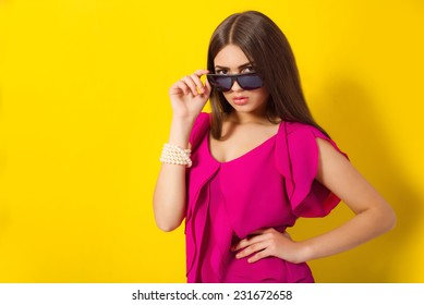 Beautiful young girl with long hair in a purple blouse with sunglasses