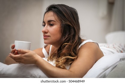 beautiful young girl with long hair lying in a white bed with white Cup in hand, closeup