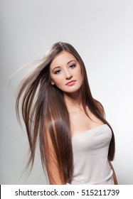 Beautiful young girl with long hair on a light background in the studio