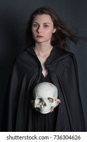 A beautiful, young girl with long hair in a black cloak with a hood, with a skull in her hands. Studio photo on a gray background. Witchcraft, necromancy, divination, Halloween.