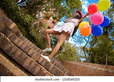 A beautiful young girl with long legs holds many colored balloons in her hand while taking us a picture in the middle of a city park.