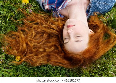 beautiful young girl with long red curly hair. hair waves lie on the green grass. top view