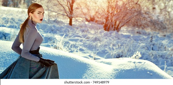 Beautiful young girl in a long winter dress in the snow..Makeup, cosmetics, make-up artist, beauty salon, hair, hairstyle, Hollywood chic, styling, stylist, hairdresser, fashion, beauty.