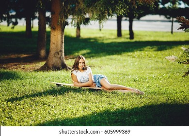 Beautiful young girl with longboard in sunny weather outdoors. Healthy lifestyle, sport