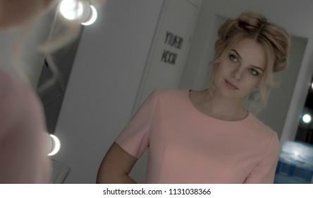 Beautiful young girl look at mirror