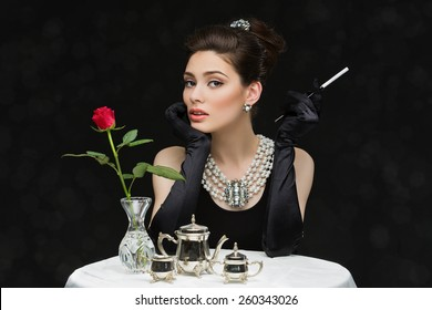 Beautiful young girl looking like audrey hepburn sitting behind table with cegarette