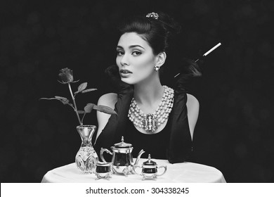 Beautiful young girl looking like audrey hepburn sitting behind table with cigarette. Black and white photo.