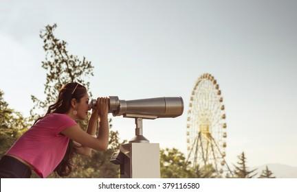 a beautiful young girl looking through binoculars