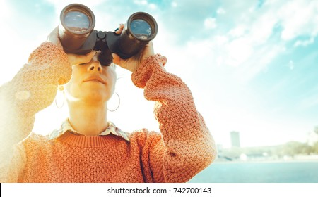 Beautiful Young Girl Looking Through Binoculars At The Sea On A Bright Sunny Day. Travel Holidays Journey Concept