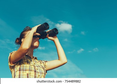 Beautiful Young Girl Looking Through Binoculars On Blue Sky Background. Travel Holidays Journey Concept