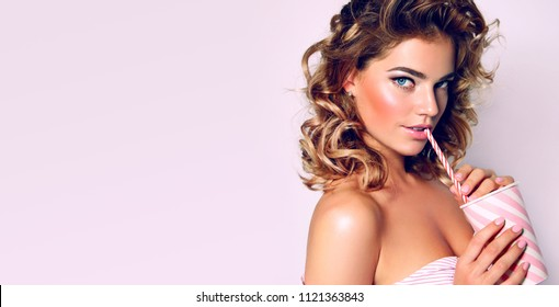 Beautiful young girl with lush hair in pink dress in pin-up style drinking milkshake through straw.Fashion, beauty, make-up, color, sales, beauty salon, make-up artist, advertising, decorations.