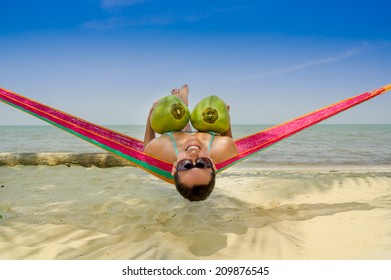 Beautiful young girl lying in a hammock holding two coconuts with sea on the background