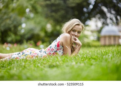 Beautiful young girl lying on the grass on a summer day