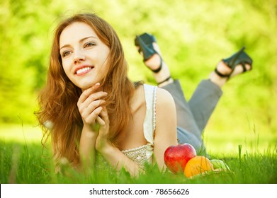 A beautiful young girl lying on the grass beside a basket of fruit is, on a background of green nature