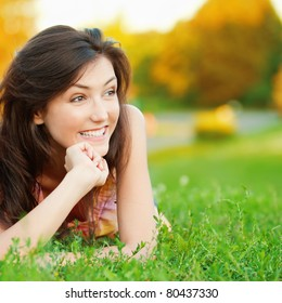 Beautiful young girl lying on the grass on a background of green nature
