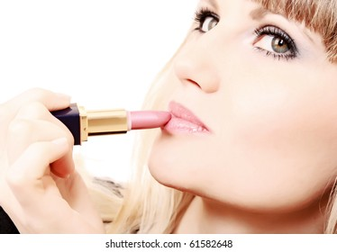 beautiful young girl making up her lips with lipstick