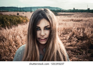 Beautiful and young girl in a man's shirt standing in the field. Halloween, girl zombie. Halloween makeup.