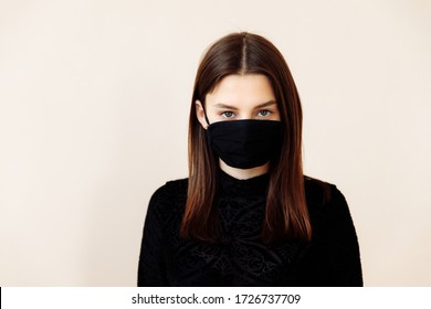 Beautiful young girl in a mask from coronavirus on a background