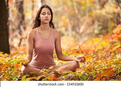 Beautiful young girl meditating in autumn park