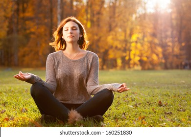 Beautiful young girl meditating in autumn park