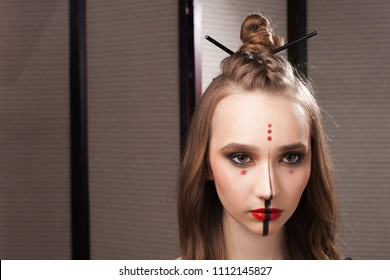 Beautiful young girl model with professional unusual mystic makeup and a coiffure with topknot and braid made by stylists in a beauty salon