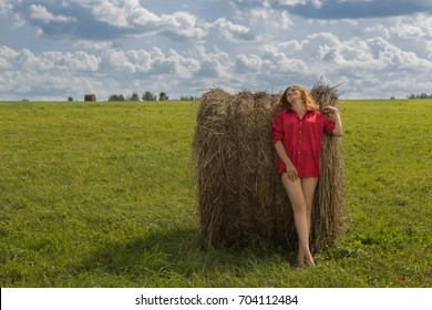 Beautiful young girl model in a red short shirt with open feet in a meadow on a green grass and with a haystack against a blue sky with clouds