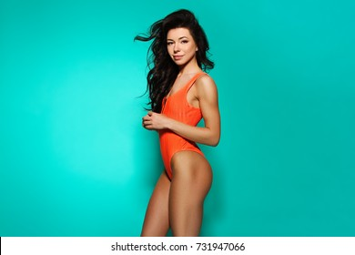 beautiful young girl model stands on blue background in sexy bathing suit