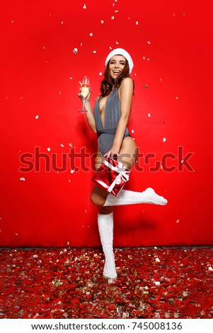 d90034631d beautiful young girl model stands on red background in sexy bathing suit  bikini and a Christmas Santa hat.on the background of flying golden candy.  - Image