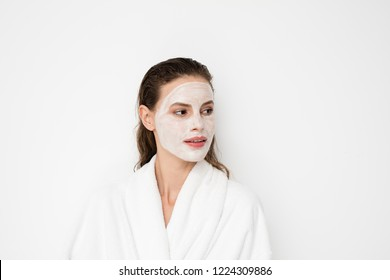 Beautiful young girl with moisturizing facial mask on white background. Photo of girl in bathrobe after shower doing her treatments. Skin care concept