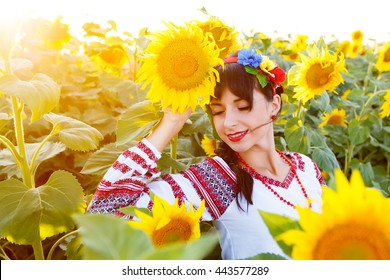 Beautiful young girl in national ukrainian blouse embrodery with closed eyes on a sunflower plant at sunset, backlight.