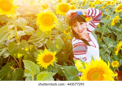 Beautiful young girl in national ukrainian blouse embrodery looking to camera on a sunflower plant at sunset, backlight.