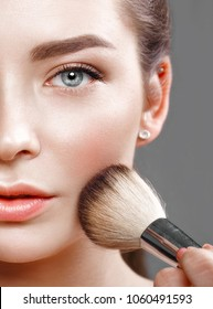 Beautiful young girl with natural nude make-up with cosmetic tools in hands. Beauty face. Photo taken in studio