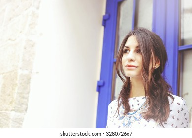 Beautiful young girl near the walls and doors. Dreamer, thoughtful girl. Space for text. Thinking about the future plans for the future. Fashionable and stylish girl. Beauty. Outdoors portrait.