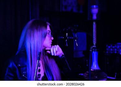 beautiful young girl in a nightclub smokes a hookah. neon light.