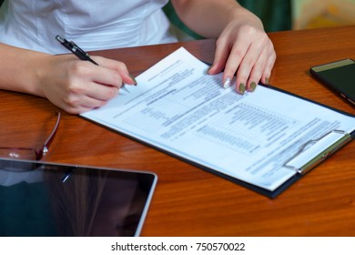 beautiful young girl office worker or business lady signs documents