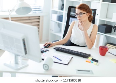 Beautiful young girl in the office working at the computer.
