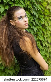 beautiful young girl on the background of the leaves in autumn day on the street with fantasy makeup in a black dress with big sexy lips