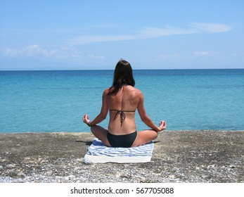 Beautiful young girl on the beach practicing yoga on a sunny day