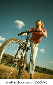 The beautiful young girl on a bicycle