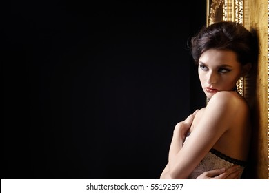 The beautiful young girl on black-gold a background