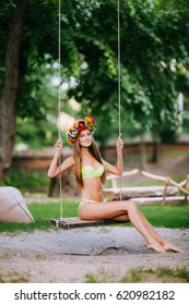 beautiful young girl on a swing on summer day outdoors.