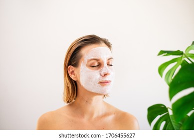 Beautiful young girl on a white background shows a white cosmetic mask on her face.