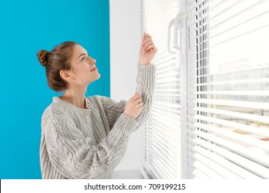 Beautiful young girl opening blinds at home