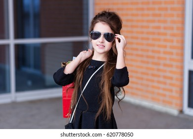 Beautiful young girl with a lot of packages at the outlet of the store. A child in sunglasses with shopping