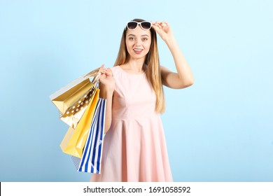 Beautiful young girl with paper bags for shopping on a colored background