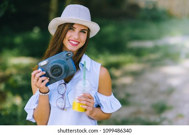 beautiful young girl in a park with a camera and juice in her hands